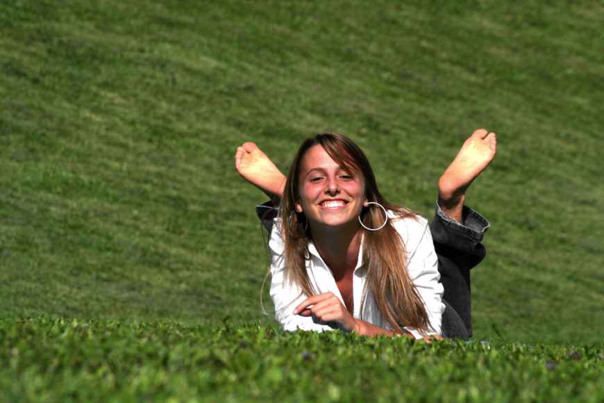 Beautiful girl smiling in the grass